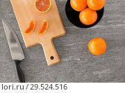 Купить «close up of oranges and knife on cutting board», фото № 29524516, снято 4 апреля 2018 г. (c) Syda Productions / Фотобанк Лори