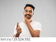 Купить «smiling indian man applying grooming oil to beard», фото № 29524592, снято 27 октября 2018 г. (c) Syda Productions / Фотобанк Лори