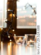 Купить «candles burning on window sill with garland lights», фото № 29524688, снято 13 января 2018 г. (c) Syda Productions / Фотобанк Лори
