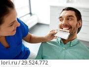 Купить «dentist choosing tooth color for patient at clinic», фото № 29524772, снято 22 апреля 2018 г. (c) Syda Productions / Фотобанк Лори