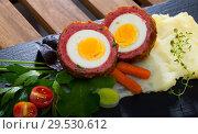 Купить «Scotch egg srved with mashed potatoes and greens, Scottish traditional dish», фото № 29530612, снято 6 июня 2020 г. (c) Яков Филимонов / Фотобанк Лори