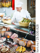 Купить «Male seller posing with wursts in butchery», фото № 29530828, снято 5 октября 2016 г. (c) Яков Филимонов / Фотобанк Лори