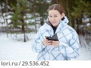 Купить «Женщина со смартфоном в руках в зимнем лесу», фото № 29536452, снято 2 января 2015 г. (c) Кекяляйнен Андрей / Фотобанк Лори