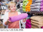 Купить «mature woman consumer holding towel», фото № 29536996, снято 29 ноября 2017 г. (c) Яков Филимонов / Фотобанк Лори