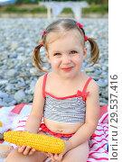 Little girl eating corn on the cob on the seaside. Стоковое фото, фотограф ivolodina / Фотобанк Лори