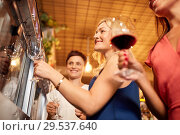 Купить «happy women pouring wine from dispenser at bar», фото № 29537640, снято 25 июня 2018 г. (c) Syda Productions / Фотобанк Лори
