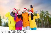 Купить «friends in santa hats and ski suits on christmas», фото № 29537724, снято 7 февраля 2015 г. (c) Syda Productions / Фотобанк Лори