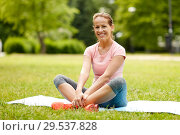 Купить «woman sitting on exercise mat at park in summer», фото № 29537828, снято 15 июня 2018 г. (c) Syda Productions / Фотобанк Лори