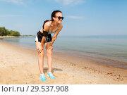 Купить «female runner with earphones and arm band on beach», фото № 29537908, снято 1 августа 2018 г. (c) Syda Productions / Фотобанк Лори