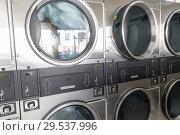 Купить «washing machines with clothes inside at laundromat», фото № 29537996, снято 28 февраля 2018 г. (c) Syda Productions / Фотобанк Лори