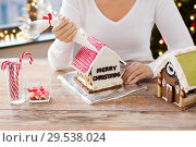 Купить «woman making gingerbread house on christmas», фото № 29538024, снято 30 октября 2014 г. (c) Syda Productions / Фотобанк Лори
