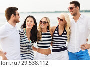 Купить «group of happy friends in striped clothes on beach», фото № 29538112, снято 13 июля 2014 г. (c) Syda Productions / Фотобанк Лори