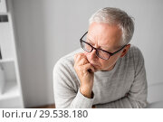 close up of senior man in glasses thinking. Стоковое фото, фотограф Syda Productions / Фотобанк Лори