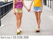 teenage girls riding skateboards in city. Стоковое фото, фотограф Syda Productions / Фотобанк Лори