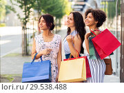 Купить «happy women with shopping bags in city», фото № 29538488, снято 22 июля 2018 г. (c) Syda Productions / Фотобанк Лори