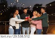 Купить «friends clinking party cups on rooftop at night», фото № 29538512, снято 2 сентября 2018 г. (c) Syda Productions / Фотобанк Лори
