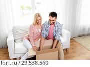 Купить «happy couple with open parcel box at home», фото № 29538560, снято 6 июня 2015 г. (c) Syda Productions / Фотобанк Лори