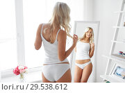Купить «woman in underwear looking at mirror in morning», фото № 29538612, снято 20 апреля 2017 г. (c) Syda Productions / Фотобанк Лори