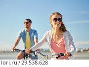 Купить «happy young couple riding bicycles at seaside», фото № 29538628, снято 23 июля 2017 г. (c) Syda Productions / Фотобанк Лори