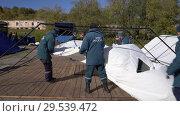Купить «Group of rescuers setting up an army field tent, deploy campground on windy day», видеоролик № 29539472, снято 2 октября 2018 г. (c) А. А. Пирагис / Фотобанк Лори