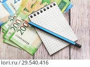 Купить «Российские деньги, блокнот для записей и карандаш. Бизнес-натюрморт», фото № 29540416, снято 7 декабря 2018 г. (c) Наталья Осипова / Фотобанк Лори