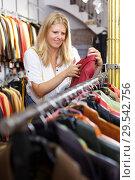 Купить «Displeased woman choosing leather clothes», фото № 29542756, снято 5 сентября 2018 г. (c) Яков Филимонов / Фотобанк Лори