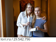 Купить «Woman with girl holding guidebook, standing in museum of art indoors», фото № 29542796, снято 21 октября 2018 г. (c) Яков Филимонов / Фотобанк Лори