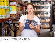 Купить «Woman standing near shelves holding notebook and samples in build store», фото № 29542816, снято 20 сентября 2018 г. (c) Яков Филимонов / Фотобанк Лори