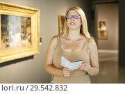 Купить «Woman with booklet looking at exhibits», фото № 29542832, снято 22 сентября 2018 г. (c) Яков Филимонов / Фотобанк Лори