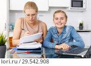 Купить «Mother checking well done home task», фото № 29542908, снято 27 сентября 2018 г. (c) Яков Филимонов / Фотобанк Лори