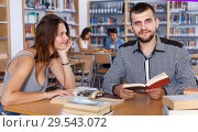 Купить «Young man and girl students studying together in public library», фото № 29543072, снято 26 июля 2018 г. (c) Яков Филимонов / Фотобанк Лори