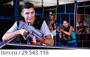 Купить «Portrait of excited guy with laser pistol playing laser tag in arena», фото № 29543116, снято 27 августа 2018 г. (c) Яков Филимонов / Фотобанк Лори