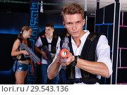 Купить «Portrait of excited guy with laser pistol playing laser tag in arena», фото № 29543136, снято 27 августа 2018 г. (c) Яков Филимонов / Фотобанк Лори