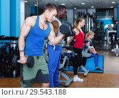 Купить «Portrait of athletic young people doing exercises with dumbbells in gym», фото № 29543188, снято 16 апреля 2018 г. (c) Яков Филимонов / Фотобанк Лори