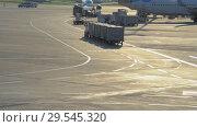 Купить «Luggage tractor carries containers on the territory of the airport Vnukovo», видеоролик № 29545320, снято 1 августа 2018 г. (c) Андрей Радченко / Фотобанк Лори