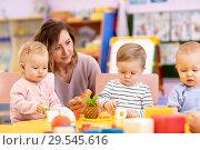 Купить «kids group playing with teacher in day care centre playroom», фото № 29545616, снято 16 декабря 2018 г. (c) Оксана Кузьмина / Фотобанк Лори