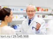 Купить «apothecary and woman with drug at pharmacy», фото № 29545908, снято 27 июня 2015 г. (c) Syda Productions / Фотобанк Лори