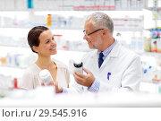 Купить «apothecary and woman with drug at pharmacy», фото № 29545916, снято 27 июня 2015 г. (c) Syda Productions / Фотобанк Лори