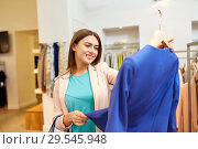 Купить «happy woman choosing clothes at clothing store», фото № 29545948, снято 19 февраля 2016 г. (c) Syda Productions / Фотобанк Лори
