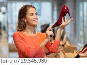 Купить «happy young woman choosing shoes at store», фото № 29545980, снято 22 сентября 2017 г. (c) Syda Productions / Фотобанк Лори
