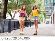 Купить «teenage girls riding skateboards in city», фото № 29546080, снято 19 июля 2018 г. (c) Syda Productions / Фотобанк Лори