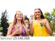 Купить «teenage girls blowing bubbles at summer park», фото № 29546088, снято 19 июля 2018 г. (c) Syda Productions / Фотобанк Лори