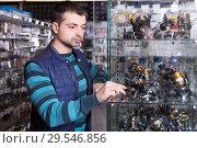 Купить «Male looking baitcasting reel for rod in the sports shop», фото № 29546856, снято 16 января 2018 г. (c) Яков Филимонов / Фотобанк Лори