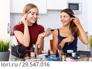 Купить «Two positive young girl friends doing make up at table with cosmetics», фото № 29547016, снято 29 августа 2018 г. (c) Яков Филимонов / Фотобанк Лори