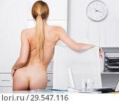 Купить «Young nude woman standing near the table and posing in the office», фото № 29547116, снято 24 апреля 2017 г. (c) Яков Филимонов / Фотобанк Лори