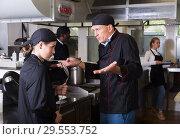 Купить «Angry chef talking to female assistant», фото № 29553752, снято 24 сентября 2018 г. (c) Яков Филимонов / Фотобанк Лори