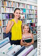 Купить «Glad woman with girl taking literature books», фото № 29553876, снято 14 декабря 2018 г. (c) Яков Филимонов / Фотобанк Лори