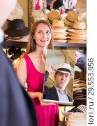 Купить «woman holding mirror and showing customer his reflection in hats shop», фото № 29553956, снято 2 мая 2017 г. (c) Яков Филимонов / Фотобанк Лори