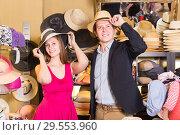 young wife and husband choosing dress hats in the store. Стоковое фото, фотограф Яков Филимонов / Фотобанк Лори
