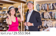 Купить «Positive woman and man trying on fashion hats», фото № 29553964, снято 2 мая 2017 г. (c) Яков Филимонов / Фотобанк Лори